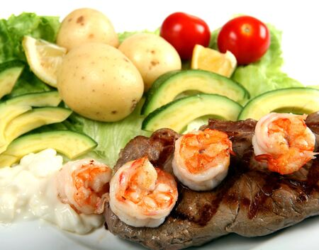 Close-up view of a surf and turf meal of grilled New York sirloin steak, prawns and salad with avacados, tomataoes, lettuce and potato, and a helping of mayonnaise. photo