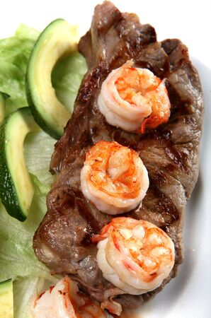 A surf and turf meal of New York striploin steak and prawns, served with salad  photo
