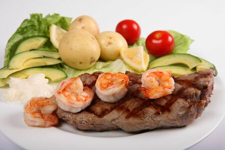 Side view of a surf and turf meal of New York steak and prawns with a salad photo