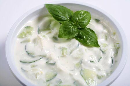 tzatziki: Arabische (of Indische) komkommer Raita - komkommers in yoghurt met knoflook en kruiden - het equivalent van de Griekse tzatziki, gegarneerd met basilicum Stockfoto
