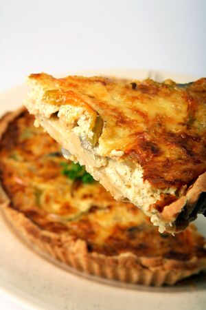capsicum: A slice of home-made onion quiche, a baked cream and egg pie topped with cheese and capsicum Stock Photo
