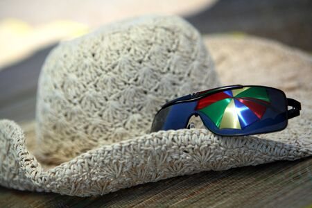 beach mat: A sunhat and sunglasses on a beach mat, with a beach umbrella reflected in the glasses and bright sun shining through it.