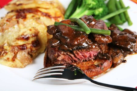 A meal of beef tournedos on a crouton, topped with mushrooms in a brown sauce and served with beans, peas and onion and potato gratin. photo