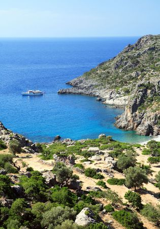 cult: A view across Lissos and its bay on the E4 long-distance path in south-west Crete, Greece, with a yacht anchored near the beach. In Roman times, the now deserted valley was an important centre for the Greek healing cult of Asklepios