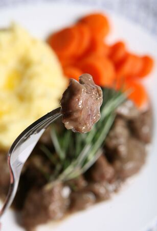 fricassee: A piece of stewed lamb in a fricassee sauce on a fork, with the meal of stew, potatoes and carrots on a plate out of focus in the background.