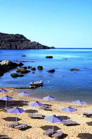 Sun umbrellas, sun loungers and a small fishing boat on the western side of Plakias, southern Crete, Greece. photo