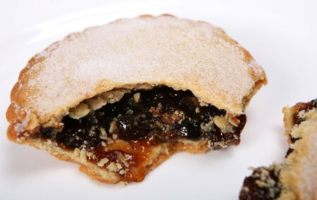 mincemeat: Close-up on a broken mince pie, a traditional Christmas treat.