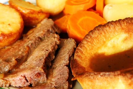 A traditional English Sunday dinner of roast beef with Yorkshire pudding, potatoes, carrots and gravy.