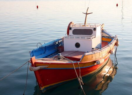 inshore: A traditional, gaily coloured Greek fishing dinghy, of the kind used daily for small-scale inshore fishing. Stock Photo