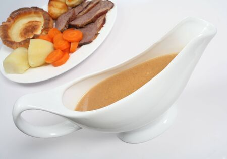 A gravy boat in front of a plate of traditional British Sunday lunch of roast beef and yorkshire pudding Stock Photo - 4084448