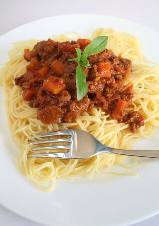 mincing: A plate of spaghetti bolognese garnished with basil, with a fork