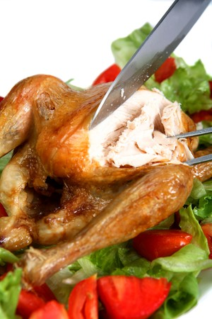 Carving a roast chicken in a bed of lettuce and tomato salad Stock Photo - 4210124