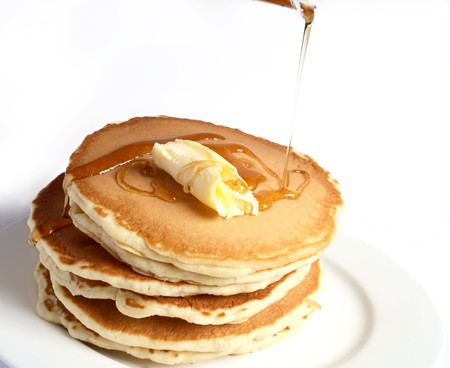dollop: A pile of pancakes with a dollop of butter and maple syrup being poured over them