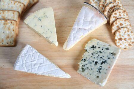 tabla de quesos: Cuatro quesos gourmet con galletas en una cheeseboard.
