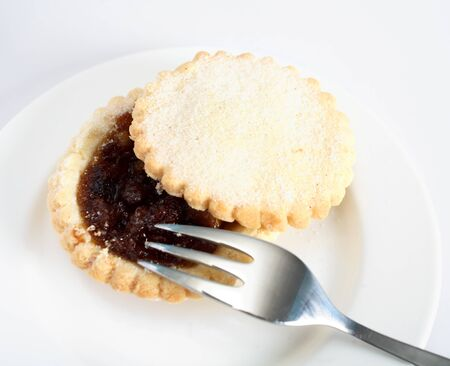 festive food: A sweet mince pie, a traditional rich festive food, on a plate with a fork.