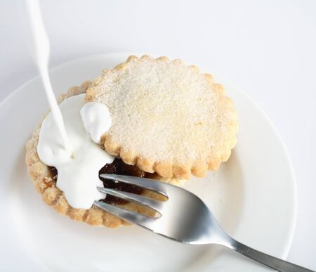festive food: Pouring cream on a sweet mince pie, a traditional rich festive food, on a plate with a fork. Stock Photo
