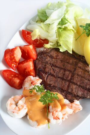 A surf and turf meal of rump steak and prawns with salad and potatoes photo