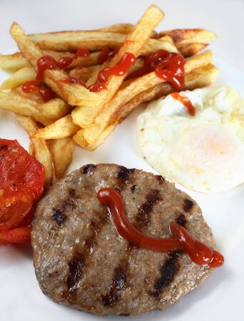 beefburger: A breakfast of grilled beefburger, fried egg, chips (or french fries) and grilled tomato, close-up Stock Photo