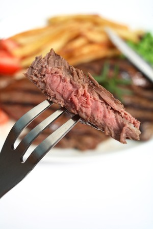 A piece of perfectly grilled steak on a fork, close-up, with the dinner plate out of focus in the background. photo