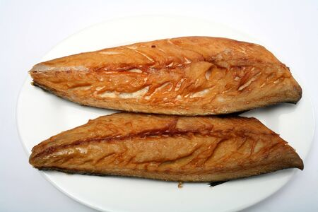 Two smoked mackerel fillets on a plate with a white background photo