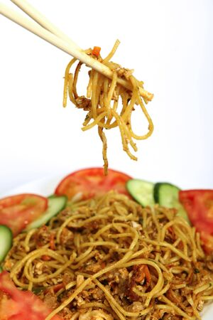 chinese noodle: A meal of chinese chicken chili and garlic noodles, being eaten with chopsticks