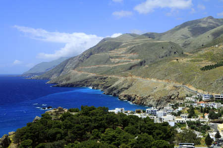 sweetwater: A view of Chora Sfakion on the south coast of crete from the east, with pale fresh water streaming out of Sweetwater Bay (Glyko Nero) and the hamlet of Loutro in the distance and the ruins of the village castle among the trees.