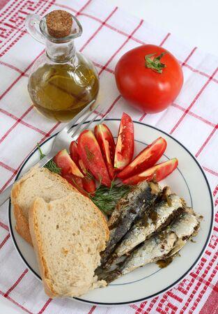 sardinas: Una comida de sardinas, pan y tomate, aderezado con eneldo y se sirve con aceite de oliva. Foto de archivo