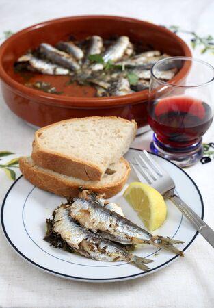 sardine: Un pasto sano di forno sardine (sarde) con pane, vino rosso e limone, Archivio Fotografico