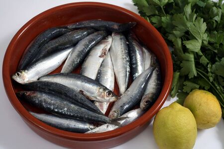 innards: Sardines (pilchards) in a rustic bowl with their heads and innards removed and lemon and parsley beside them. Sardines, a common part of the mediterranean diet, are very high in Omega-3 oils and Vitamin D, making them one of the healthiest foods.