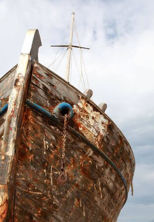 The paint-stripped remains of a large wooden ship rot against a cloudy sky, even the string used in caulking the timbers is falling from between them. photo