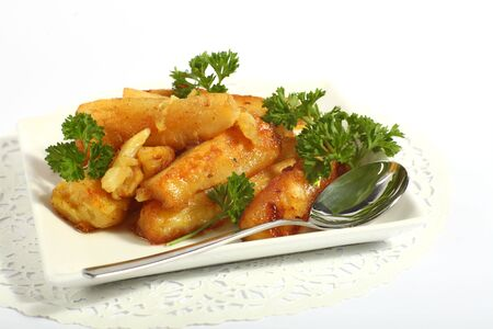parsnips: A bowl of honey-glazed roasted parsnips with a serving spoon