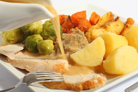 stuffing: Pouring gravy on a festive turkey meal, with roast yams, roast parsnips, boiled potatoes and stuffing