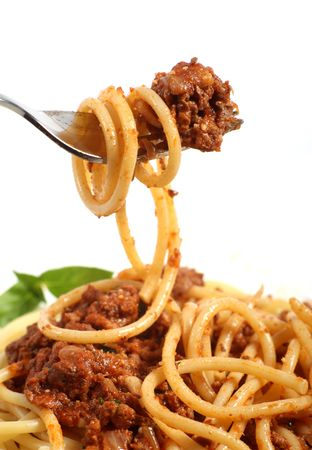 bolognese: A fork lifting spaghetti bolognese above a plate of the same