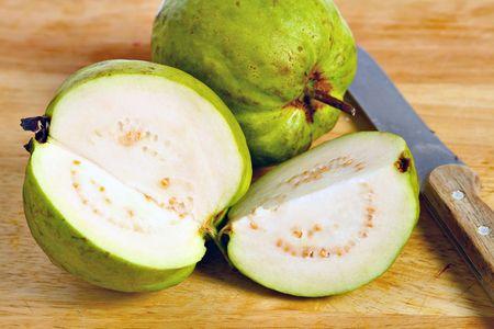 Un frutto tropicale, del comune mela guaiava (Psidium guajava) varietà, sezionato per mostrare la carne e semi all'interno Archivio Fotografico - 5672423