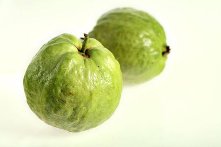 superfruit: Two quava fruits over a white background, fruit of the shrub Psidium guajava. Wikipedia notes that guava is often sold as a superfruit because of its antioxidants, omega-3 , -6 and polunsaturated fatty acids, etc. Stock Photo