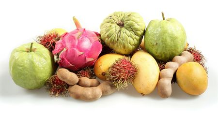 dragonfruit: Side view of a pile of tropical fruits with shadow on a white background, comprising dragonfruit, custard apple, guava, tamarind, mango. Stock Photo