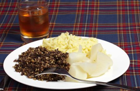 burns night: Haggis, turnips, mashed potatoes and a glass of whisky on a tartan background - the ingredients for a Burns Night supper