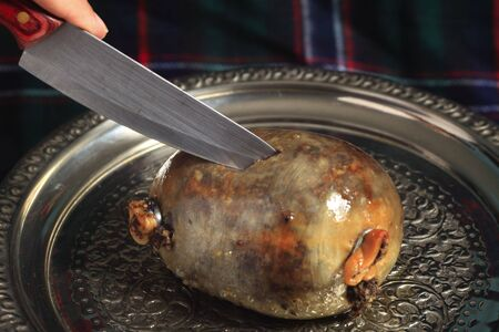 offal: A haggis on a silver tray being cut, a highlight of a Burns Night supper following the