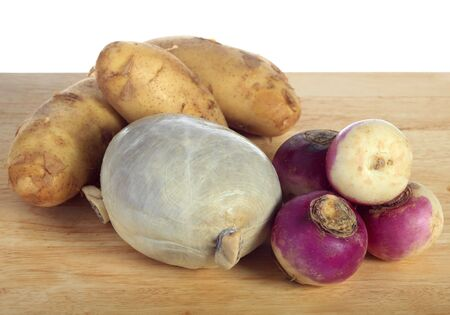 neeps: A traditional Scottish haggis, a sheeps stomach stuffed with chopped offal and barley, on a chopping board with turnips and potatoes, the traditional ingredients of a Burns Night Supper