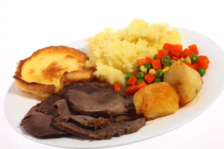 A plate of roast beef with mixed vegetables and roasted and mashed potatoes, at an angle. photo