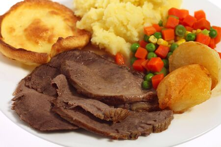 british foods: A meal of roast beef yorkshire pudding and vegetables