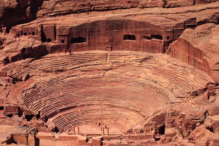 sightseers: An aerial view of the Roman-era amphitheater carved into the pink sandstone at Petra, Jordan. The building facades cut into the rock behind are ancient graves. Stock Photo