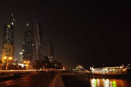 A night-time view of the Doha Corniche, Qatar, Arabia, with it's towers and pleasure dhows, January 2010. Time exposure, people blurred beyond recognition.