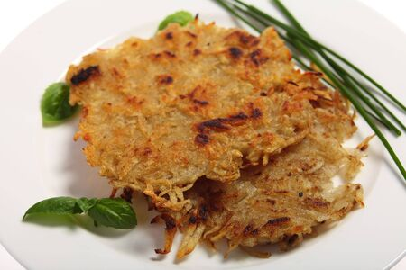 Traditional rosti potatoes in the Swiss style, garnished with chives and basil Stock Photo