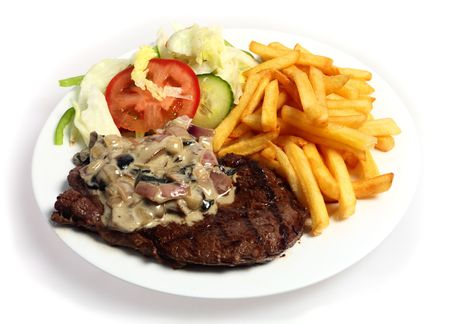 A meal of grilled steak topped with a mushroom and onion in cream sauce, served with French fried potato chips and a salad