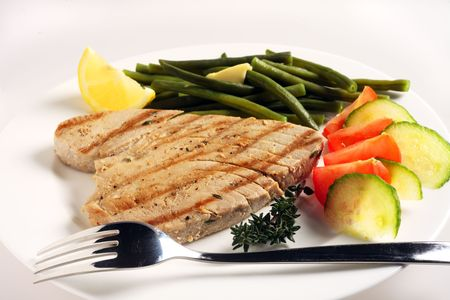 tuna: A meal of grilled tuna steak with a salad of tomato and cucumber and green beans, garnished with a sprig of thyme and a lemon wedge