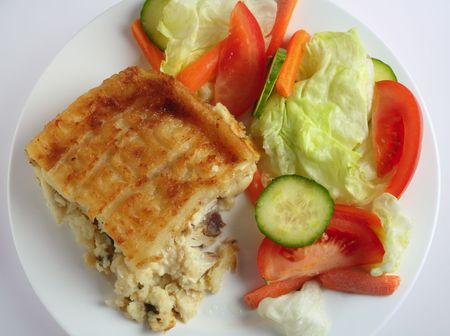 english cucumber: Traditional seafood pie, with fish in bechamel sauce topped with mashed potato and baked, served with a salad, high angle view Stock Photo