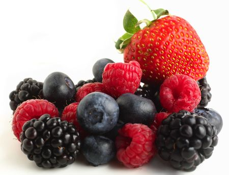 A pile of berry fruits, blueberries, raspberries, blackberries and a strawberry, against a white background. Stock Photo