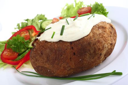 russet potato: A baked Russet potato topped with a cream cheese, herbs and chives mixture, served with a garden salad.