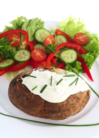 russet potato: A baked Russet potato topped with a cream cheese and chives mixture, served with a fresh salad Stock Photo